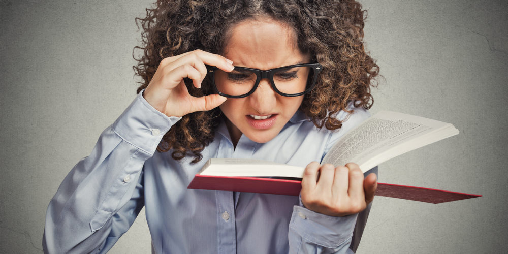 Closeup portrait young woman with eye glasses trying to read book, having difficulties seeing text, bad vision sight problem isolated grey background. Face expression reaction health eyesight issues